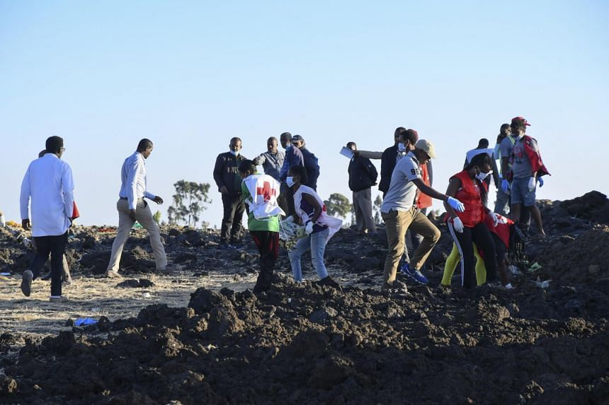 Rescue workers carry wreckage at the crash site of Ethiopia Airlines Boeing 737 Max 8, near Bishoftu, Ethiopia, on March 10, 2019.