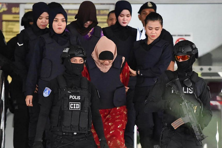 Siti Aisyah (centre) and Doan Thi Huong (top, centre) are escorted by Malaysian police after a special court session to rule on witness statements, on Dec 14, 2018 for their alleged role in the assassination of Kim Jong Nam.