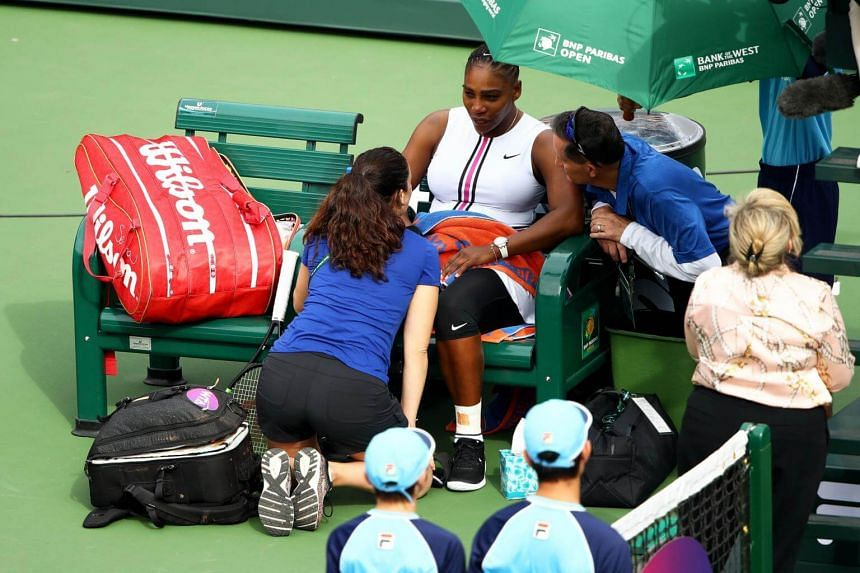 Serena Williams sits down with medical staff before retiring from her third-round WTA match at Indian Wells on March 10, 2019.