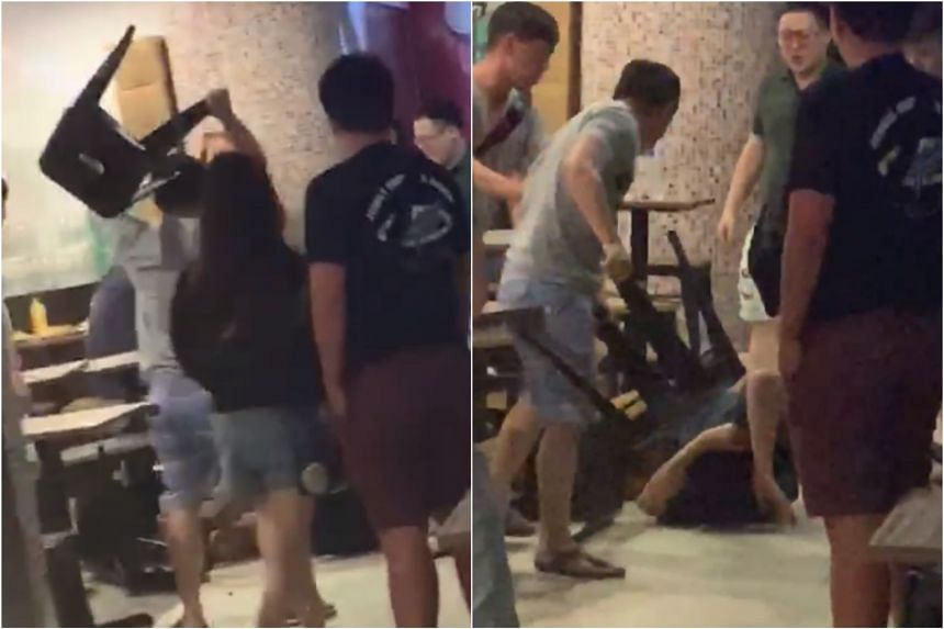 In the video, a man is seen using a stool from the foodcourt to hit another man lying on the ground.
