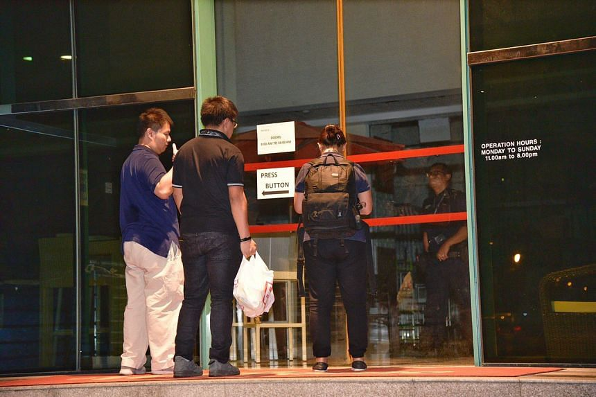 Police officers entering the premises where a 23-year-old man was arrested after one man was found dead and another injured at a building along Sungei Kadut Loop on March 11, 2019.