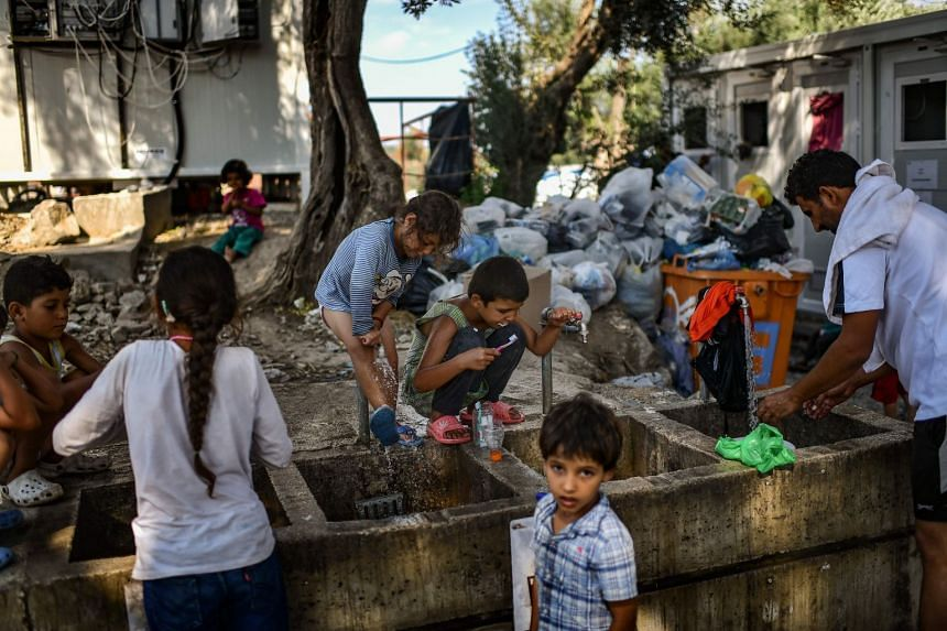 Refugees and migrants clean themselves and wash their clothes at a Lesbos camp.