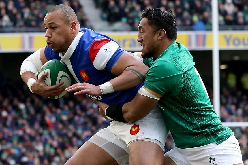 France's centre Gael Fickou (left)) is tackled by Ireland's centre Bundee Aki.