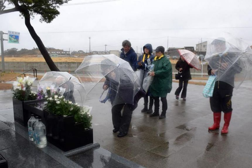 People pray in front of a memorial monument in Soma, Fukushima Prefecture on March 11, 2019 on the eighth anniversary of the 2011 tsunami disaster.