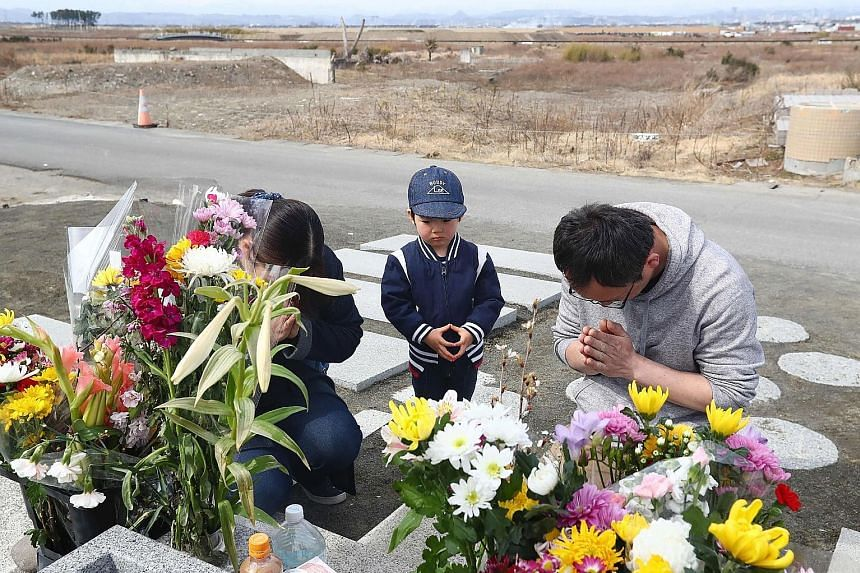 A family paying their respects to the victims of the 2011 earthquake, tsunami and Fukushima nuclear disaster in Japan.