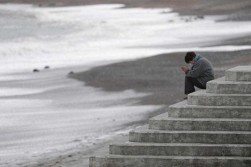 A woman facing the sea to pray while mourning the victims of the 2011 earthquake, tsunami and nuclear disaster in Japan that left about 18,500 people dead or missing.