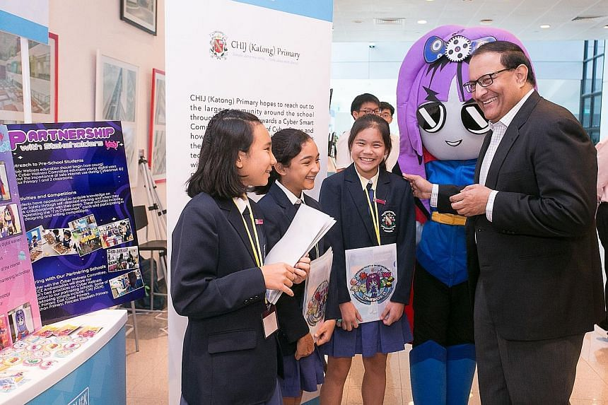 Mr S. Iswaran interacting yesterday with student exhibitors from CHIJ (Katong) Primary School at the Better Internet Conference 2019. The exhibition showcased 11 projects supported by the Media Literacy Council.