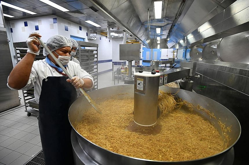 Members of Sats' kitchen crew dishing nasi goreng (above) into the thermoforming line to extend the shelf life of the food, and using an auto-fryer to cook a large batch of noodles (left) in the extended kitchen facility at Changi North.
