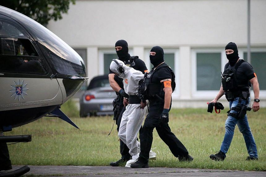 Police officers of a special unit escort Iraqi asylum seeker Ali Bashar, who is suspected of having killed a German teenage girl, to a helicopter in Wiesbaden, on June 10, 2018.
