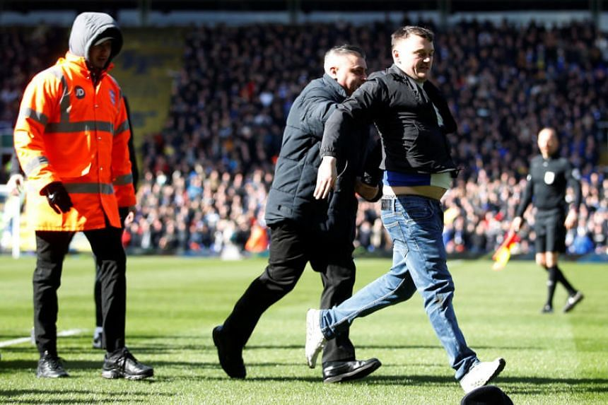 Birmingham City fan Paul Mitchel (right) being led off after he ran onto the pitch and punched Aston Villa captain Jack Grealish at St Andrew's stadium in Birmingham on March 10, 2019.
