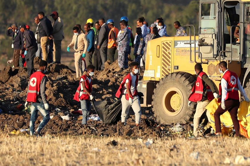 Members of the search and rescue mission removing bodies from the crash site of Ethiopian Airlines Flight ET302. All 157 people on board the flight were killed in Sunday's crash.