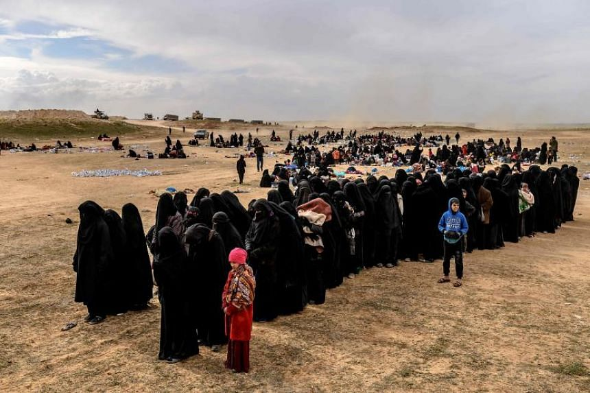 Civilians evacuated from the Islamic State group's embattled holdout of Baghouz wait at a screening area held by the US-backed Kurdish-led Syrian Democratic Forces, in the eastern Syrian province of Deir Ezzor, on March 5, 2019.