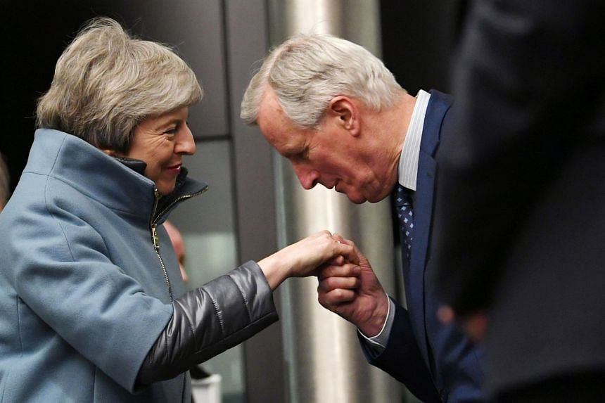 Michel Barnier kissing Theresa May's hand as she arrives at the European Parliament, March 11, 2019.