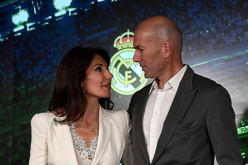 Real Madrid's newly appointed coach Zinedine Zidane posing with his wife Veronique after giving a press conference on Monday. The Frenchman has signed a three-year contract, just nine months after he resigned from the club, having led them to an hist