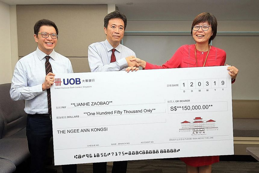 Ngee Ann Kongsi vice-president Jamie Teo (far left) and president Richard Lee handing over a cheque yesterday to Ms Lee Huay Leng, head of SPH's Chinese Media Group. The beneficiaries will receive free print subscriptions to Lianhe Zaobao for a year.