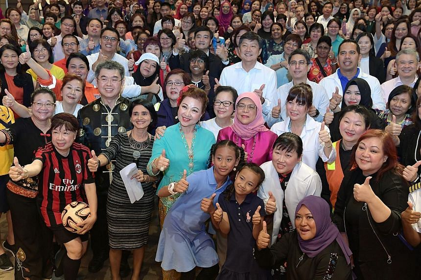 President Halimah Yacob (centre, in pink) at the forum marking International Women's Day, with NTUC secretary-general Ng Chee Meng and Associate Professor Faishal Ibrahim, Senior Parliamentary Secretary for Social and Family Development (both behind
