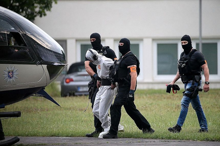 German police officers escorting Ali Bashar to a helicopter after a court appearance in Wiesbaden last June. The Iraqi asylum seeker allegedly beat, raped and strangled 14-year-old schoolgirl Susanna Maria Feldman to death in a wooded area near his r