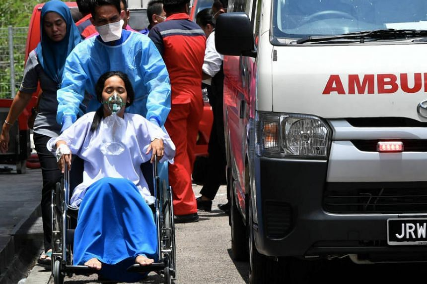 A student, one of 20 affected by toxic fumes caused by chemicals dumped into the Sungai Kim Kim river in Pasir Gudang, being wheelchaired into a hospital in Johor Baru on March 13, 2019.
