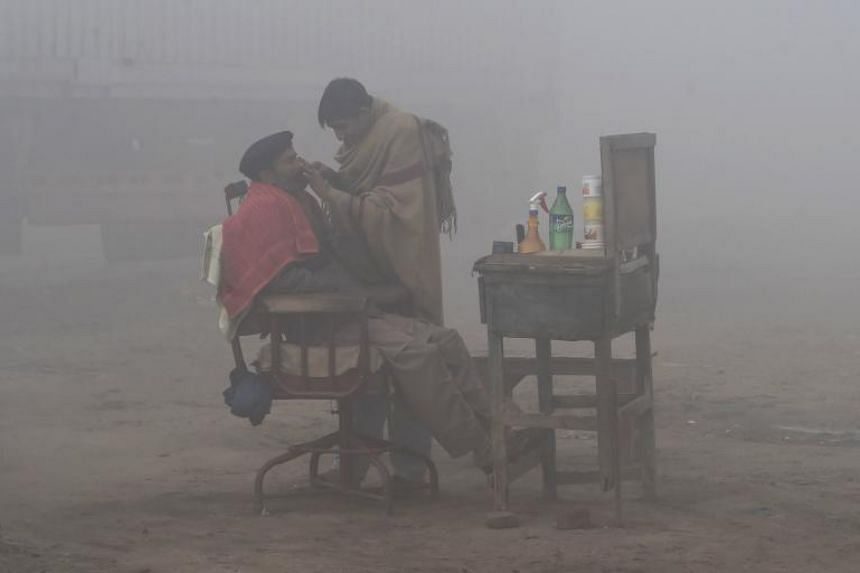 A Pakistani barber shaves a customer alongside a road amid heavy fog and smog conditions in Lahore on January 24, 2019. Deadly smog-incuding emissions are one of the problems driving a worldwide epidemic that hampers the global economy, said the Unit