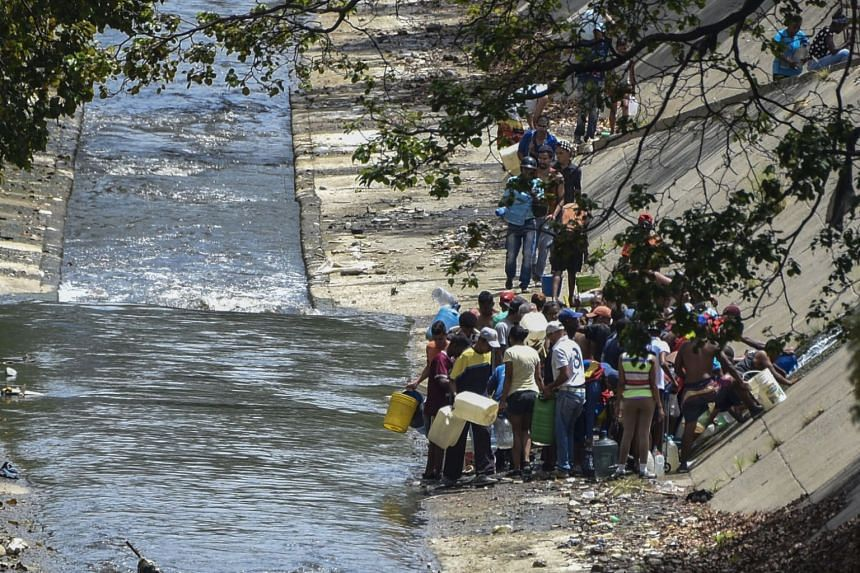 People collecting water from a broken pipe flowing into a sewage canal at the Guaire river in Caracas, on March 11, 2019.