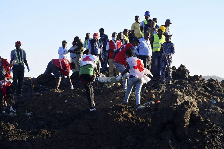 Rescue workers carrying wreckage of the Ethiopia Airlines Boeing 737 Max 8 that crashed, near Bishoftu, Ethiopia, on March 10, 2019.
