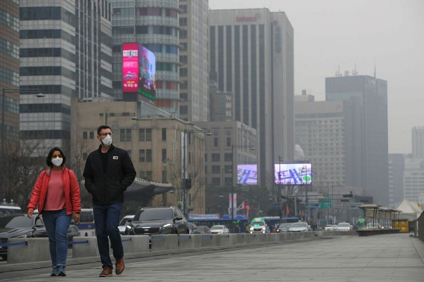 Pedestrians wearing face masks as they walk through Gwanghwamun square amid pollution in central Seoul, on March 6, 2019.