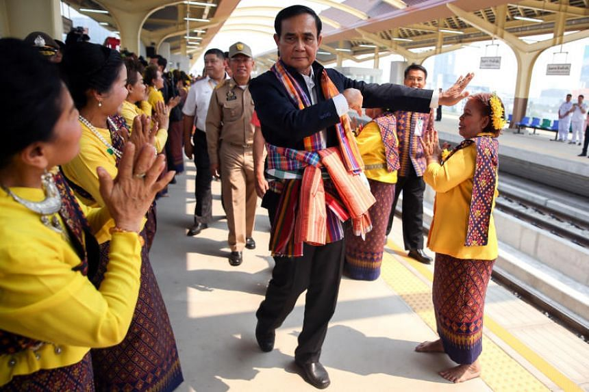Thailand's Prime Minister Prayut Chan-o-cha performs a traditional dance with performers at Khon Kaen railway station during a visit ahead of the general election in Khon Kean province, Thailand, March 13, 2019.