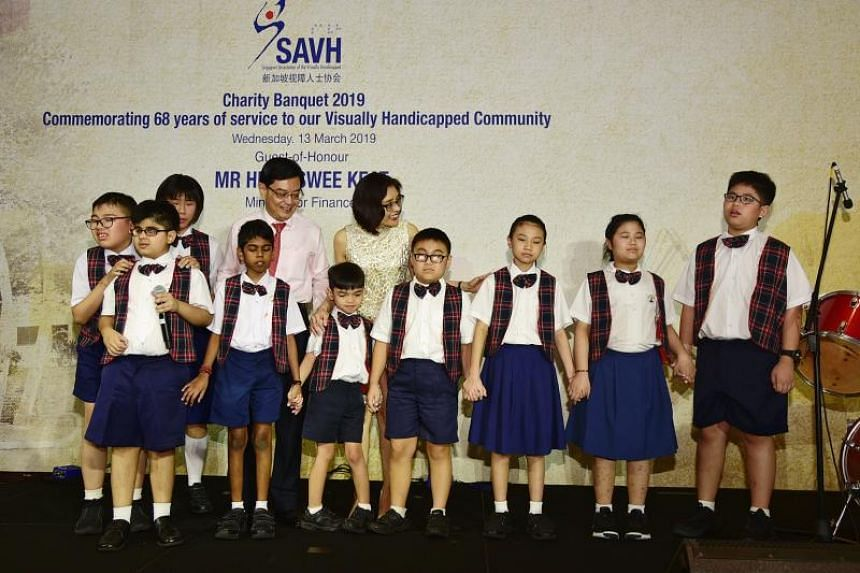 Finance Minister Heng Swee Keat and his wife Chang Hwee Nee, CEO of the National Heritage Board, with children from the Lighthouse School choir during a fundraising dinner for the Singapore Association of the Visually Handicapped on March 13, 2019.