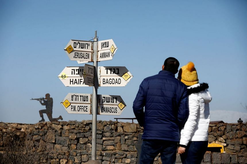 A couple look at signs pointing out distances to different cities, at an observation post in the Golan Heights.