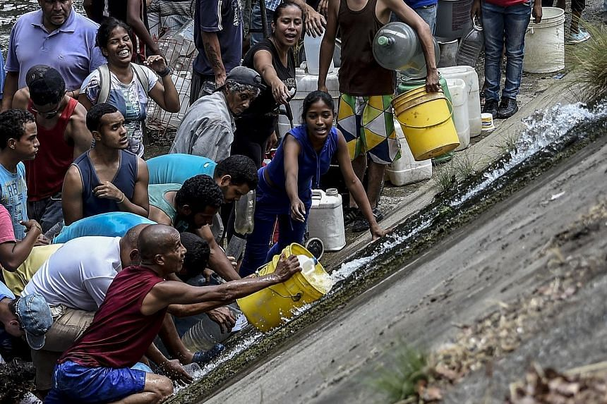 Caracas residents scrambling to collect water from a burst water pipe that is flowing into a sewage canal at the Guaire River.