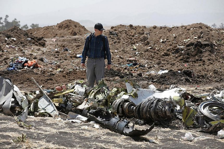 An investigator at the scene of the Ethiopian Airlines crash near the town of Bishoftu, south-east of the country's capital Addis Ababa, on Tuesday. All 157 people aboard Flight 302 bound for Nairobi were killed in the crash on Sunday.