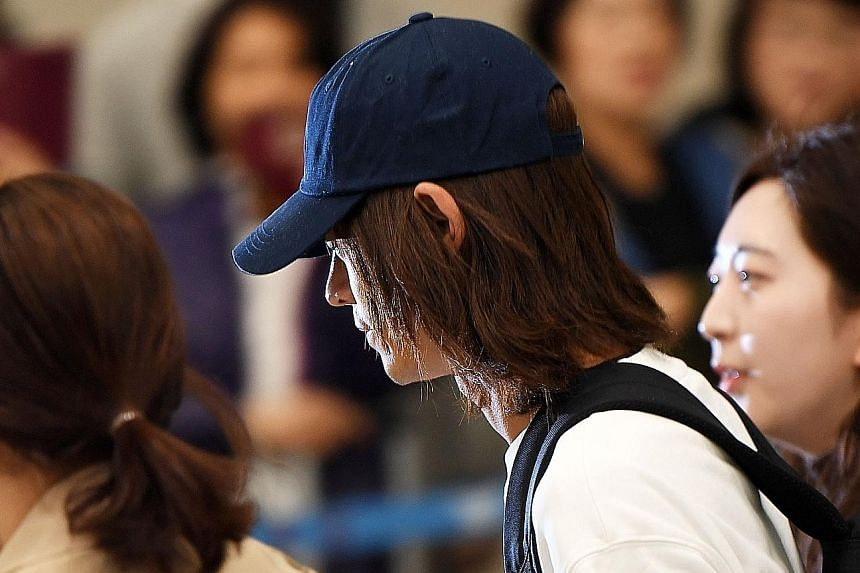 K-pop singer Jung Joon-young surrounded by reporters as he arrives at Incheon International Airport on Tuesday.