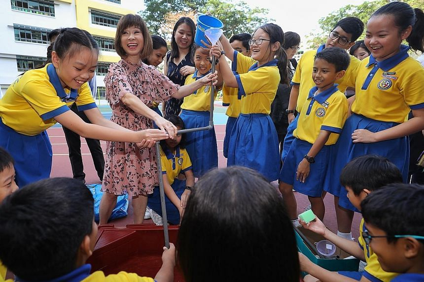 Dr Amy Khor, Senior Minister of State for the Environment and Water Resources, joining Clementi Primary pupils in a water-pipe game during a water-conservation exercise held at the school yesterday. Dr Khor says such exercises teach pupils to make ev