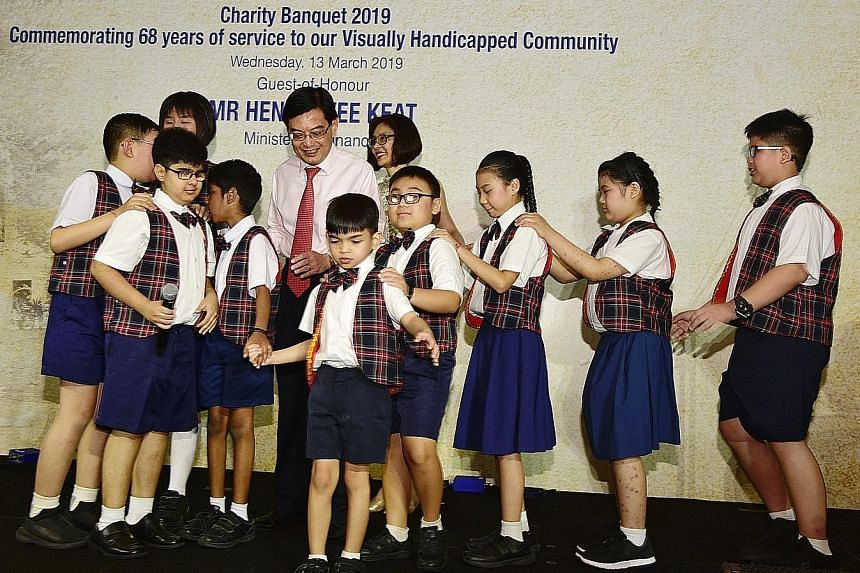 Finance Minister Heng Swee Keat and his wife Chang Hwee Nee with pupils from Lighthouse School, which provides special education to children with visual impairment and hearing loss. The pupils sang at a fund-raising dinner for the Singapore Associati