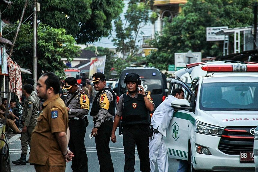 Indonesian policemen outside a house in Sibolga, North Sumatra, where a woman detonated a bomb, killing herself and her young child, yesterday. She was the wife of a militant who had been arrested the day before.