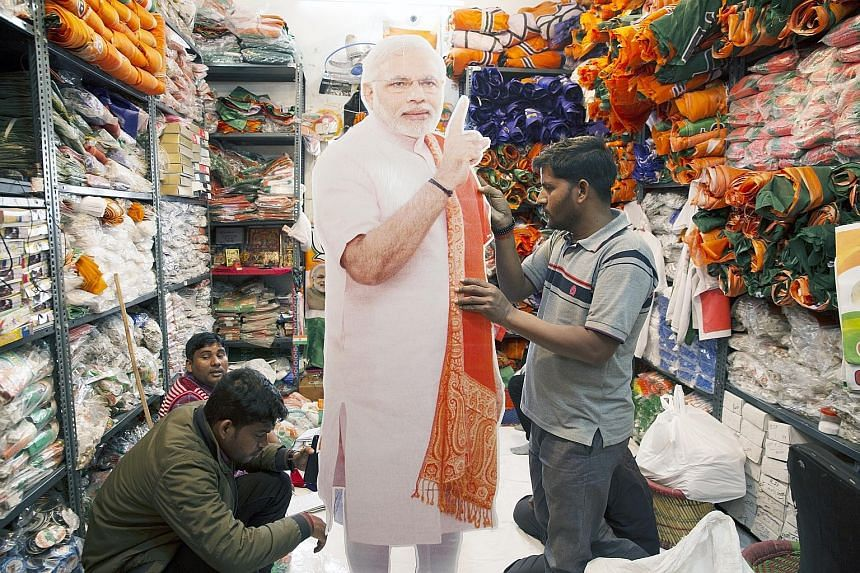 Workers with a cut-out of India's Prime Minister Narendra Modi at a store in New Delhi. The country's 900 million voters will be casting their ballots between April 11 and May 19.