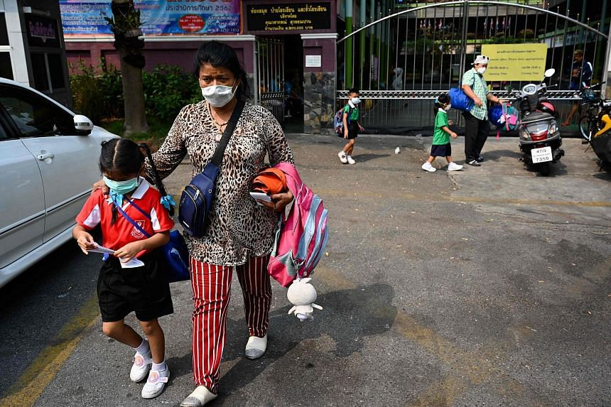 A woman picks up a child from school early due to pollution in Bangkok, on Jan 30, 2019.