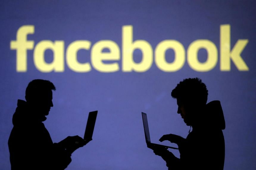 Silhouettes of laptop users seen next to a screen projection of the Facebook logo, on March 28, 2018.