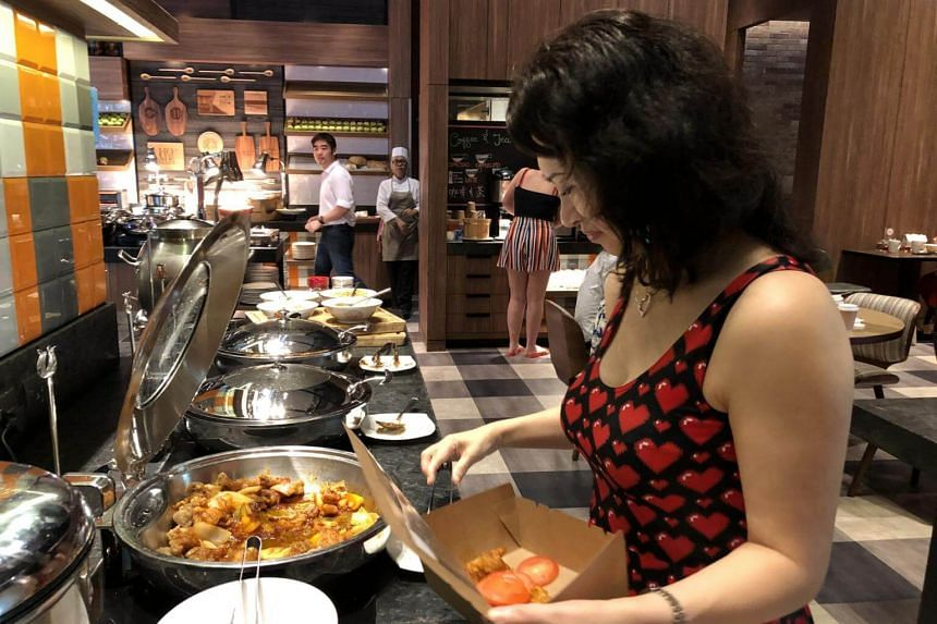Ms Mary Miao, a Treatsure user, packs a boxed meal at J65 in Hotel Jen Tanglin.
