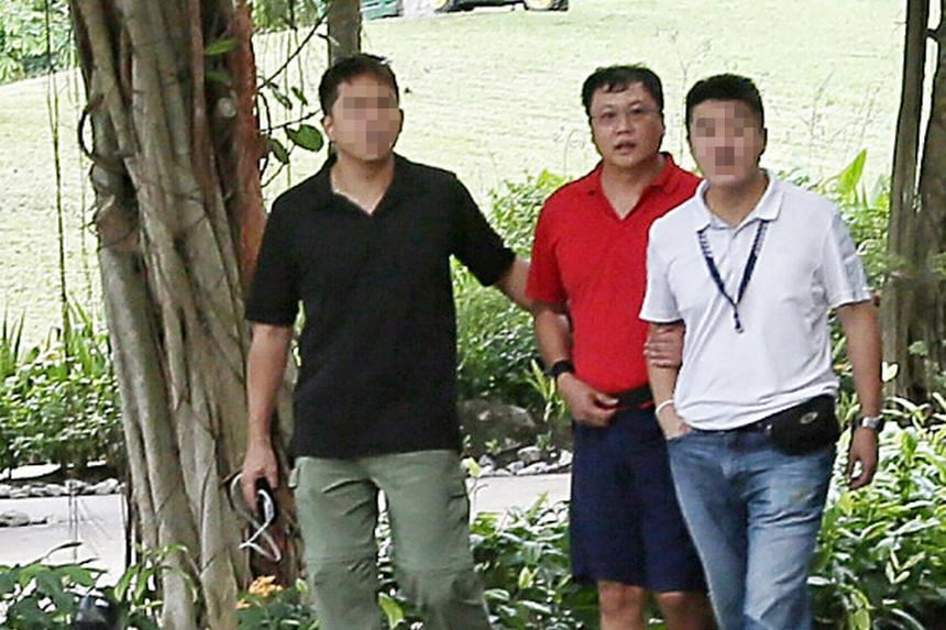 Murder suspect Leslie Khoo Kwee Hock (in red) was taken to Gardens by the Bay, the scene of the alleged crime.