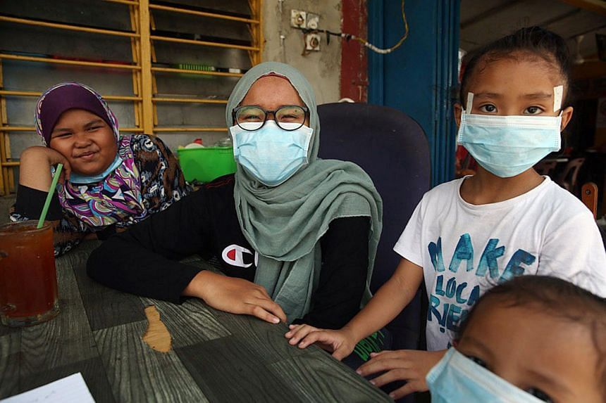 Farra Hafiqa Md Izamkhir (centre) fell ill on March 11 after noticing a foul smell during physical education class. She began vomiting and fainted. Some of her friends were warded in ICU at a hospital near Kampung Pasir Putih, in Pasir Gudang.