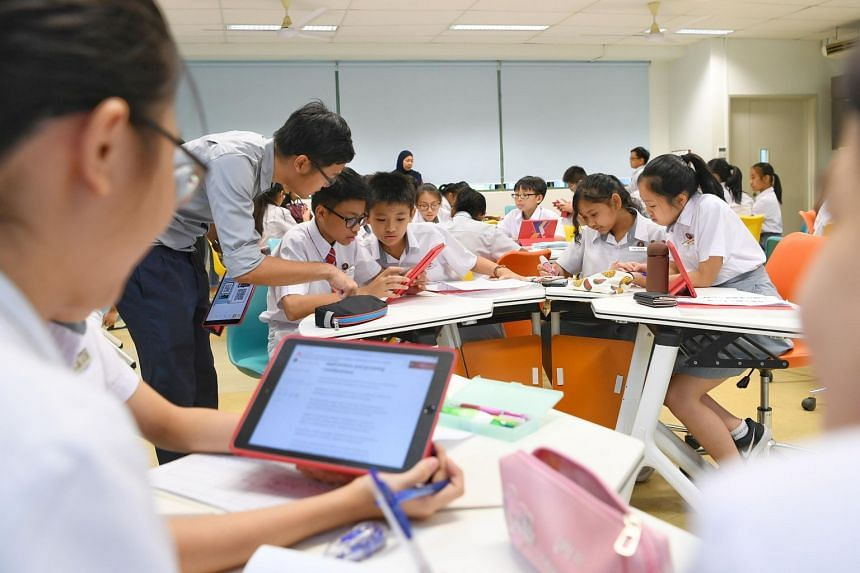 Secondary school students having a lesson with electronic devices in a classroom.