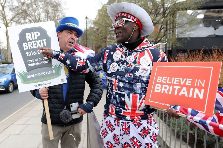 Anti-Brexit campaigner Steve Bray (L) talks with pro-Brexit supporter Joseph Afrane as they walk near the Houses of Parliament in London.