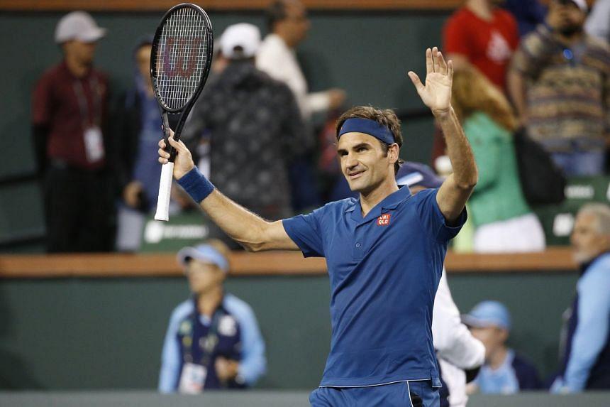 Federer celebrates victory after defeating compatriot Stan Wawrinka.