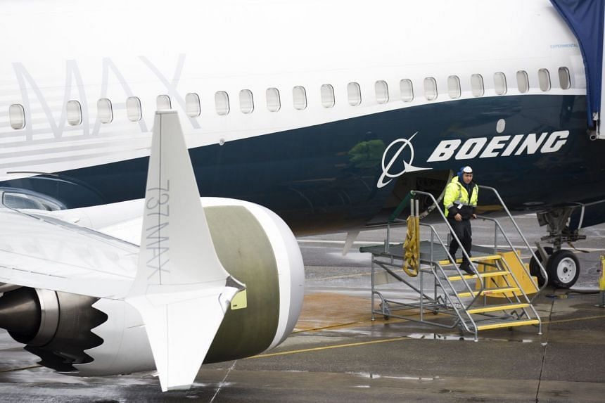 A worker is pictured next to a Boeing 737 Max 9 plane on the tarmac at the Boeing Renton Factory in Renton, Washington.