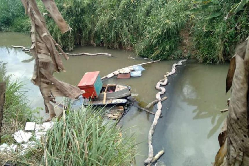 Part of the Sungai Kim Kim river in Pasir Gudang undergoing a clean-upon March 8, where oil booms have been fitted to stop the oily substance from floating further.