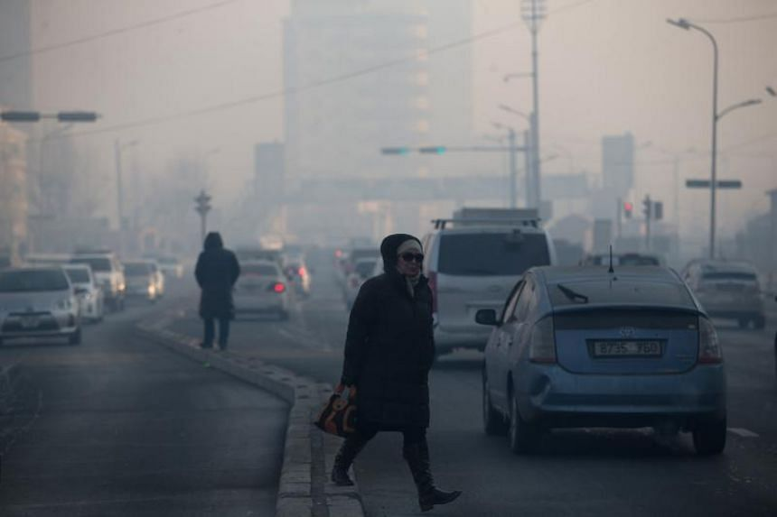 A woman walking across a road on a polluted day in Ulaanbaatar, the capital of Mongolia on February 14, 2019.