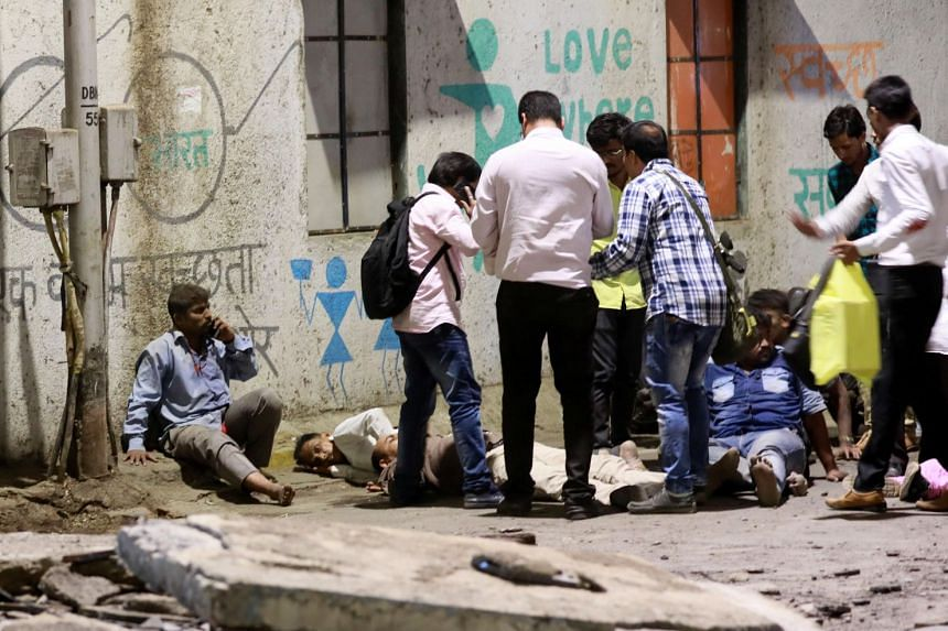 Injured people wait for medical assistance after a footbridge collapsed in Mumbai.