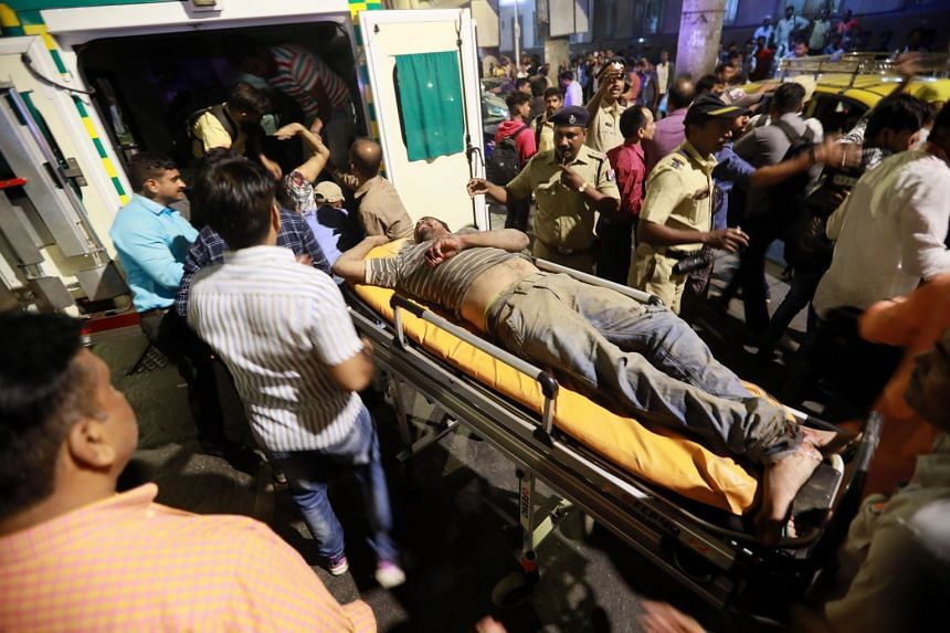 Injured people are rushed to an ambulance after a footbridge collapsed in Mumbai.