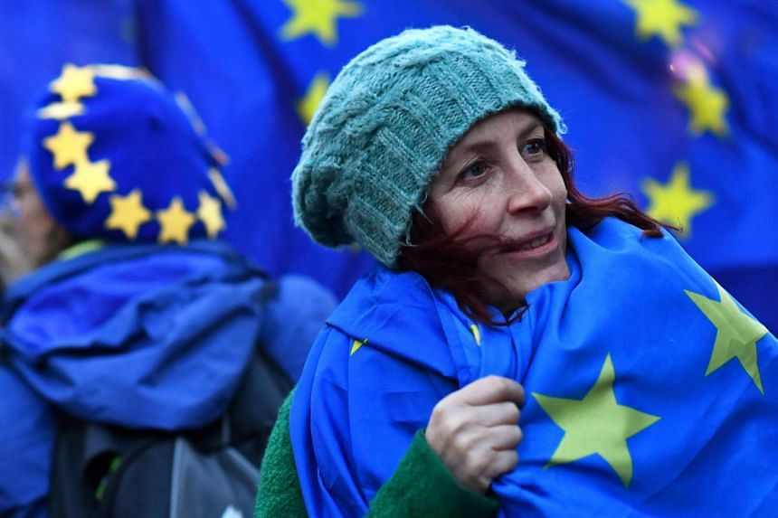 An anti-Brexit protester wears an EU flag outside Parliament in London, March 14, 2019.